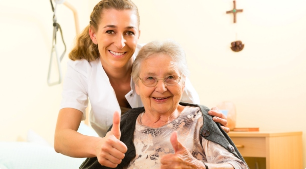caregiver and a senior woman showing thumbs up